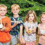 four children holding plant pots